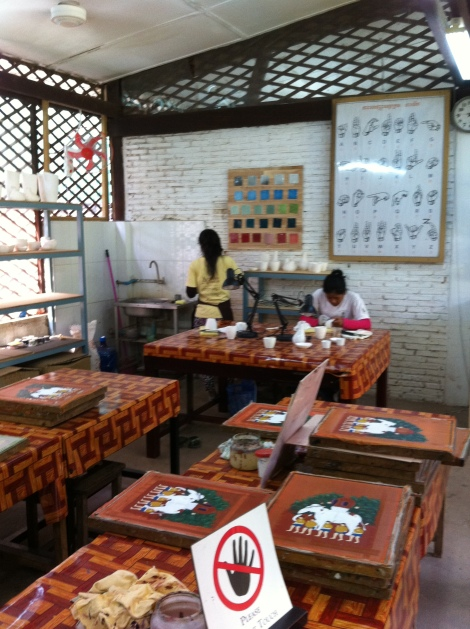 Artistas surdo-mudos elaboram pinturas em quadros no Artisan Angkor.