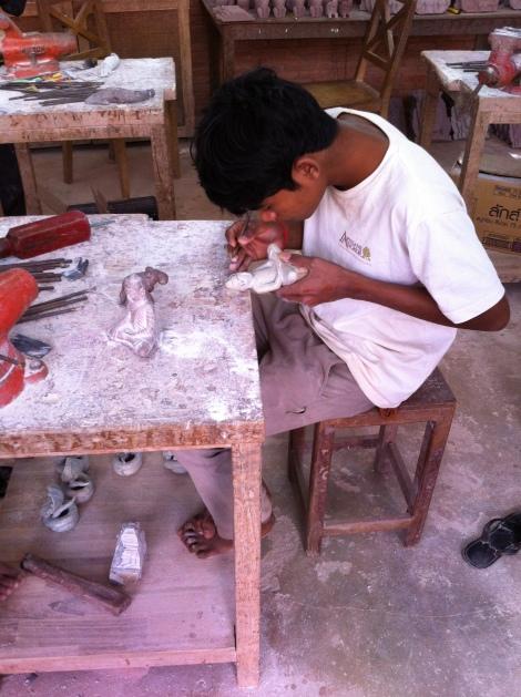 Jovem artesão esculpindo um Buda.