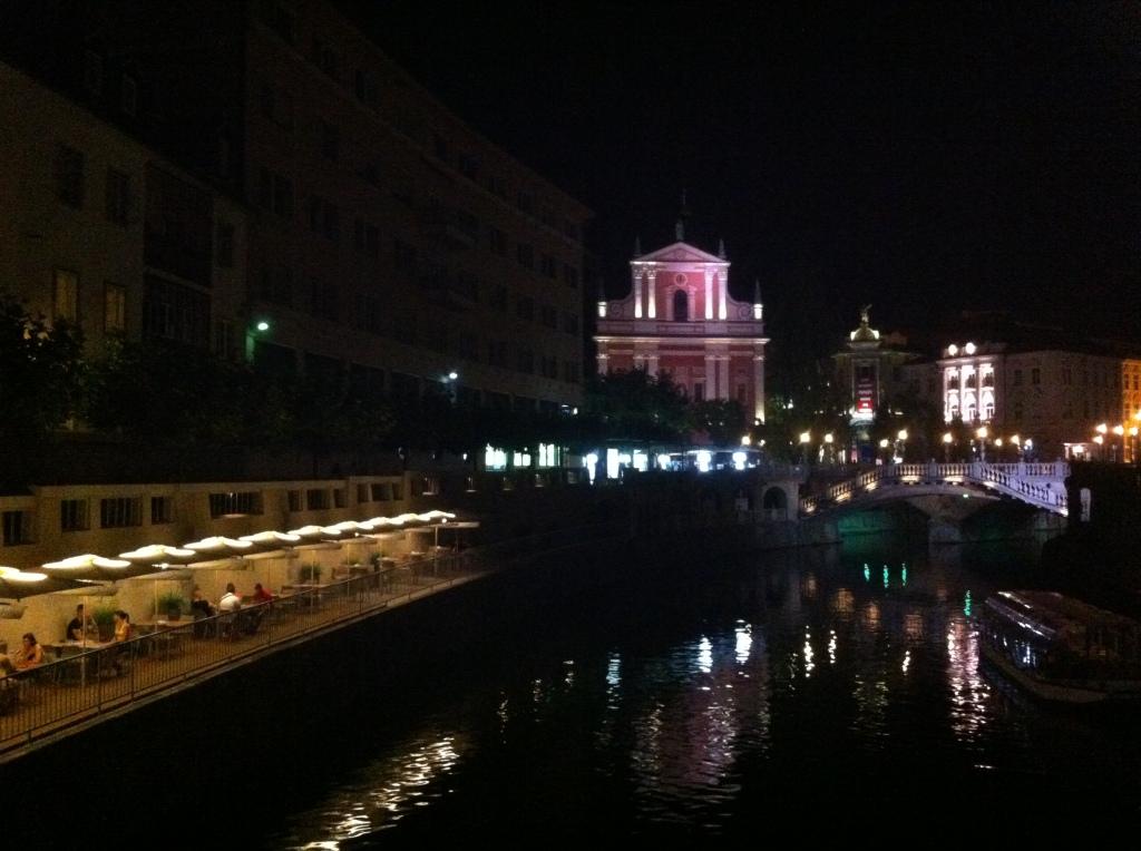 Catedral ao fundo e restaurantes a beira do canal do rio Ljubliana.